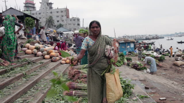 woman collecting vegetables at the vegetable market on buriganga river bank, not far from the sadarghat boat terminal, dhaka, bangladesh, indian sub-continent, asia - dhaka stock-videos und b-roll-filmmaterial