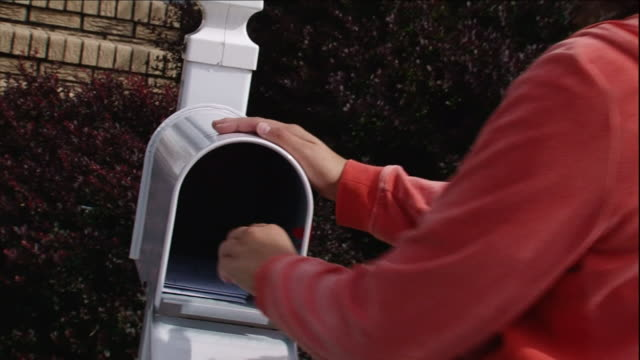 a woman collects mail from a mailbox. - letterbox点の映像素材/bロール