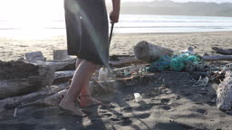 Woman collects plastic garbage from beach