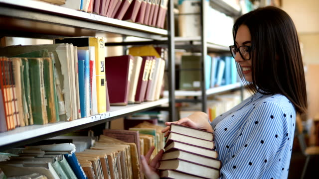 Woman college student working at library holds bunch of books in hands, looking smart. bookshelves at the library.