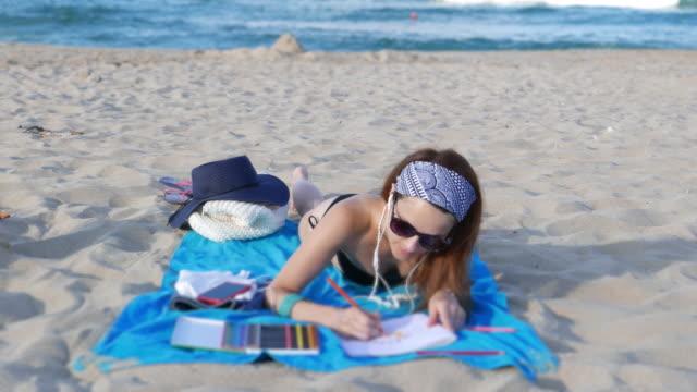 女性のビーチでストレス本アンチ着色 - ゼンタングル模様点の映像素材/bロール