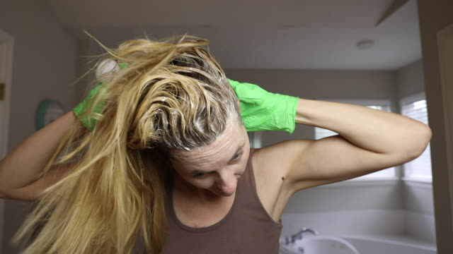woman coloring hair roots at home - domestic bathroom stock videos & royalty-free footage