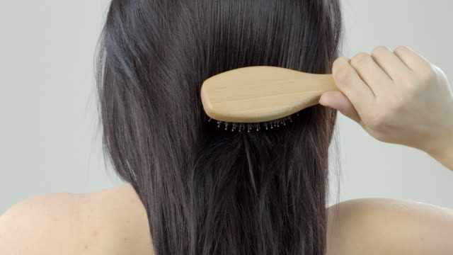 stockvideo's en b-roll-footage met woman combing her long hair with hairbrush - haarborstel