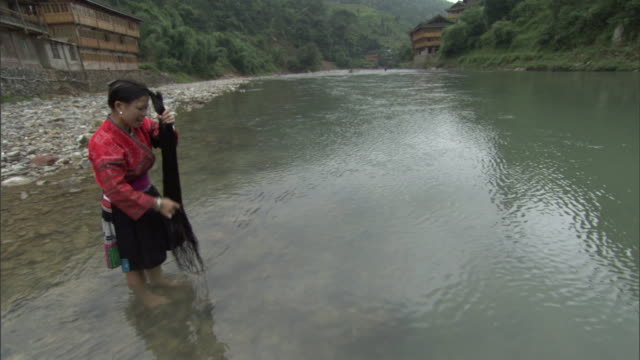 a woman combs and twists her long hair while standing in a river. - combing stock videos & royalty-free footage