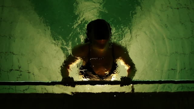 woman comes up from the water in an illuminated swimming pool - floating on water stock videos & royalty-free footage