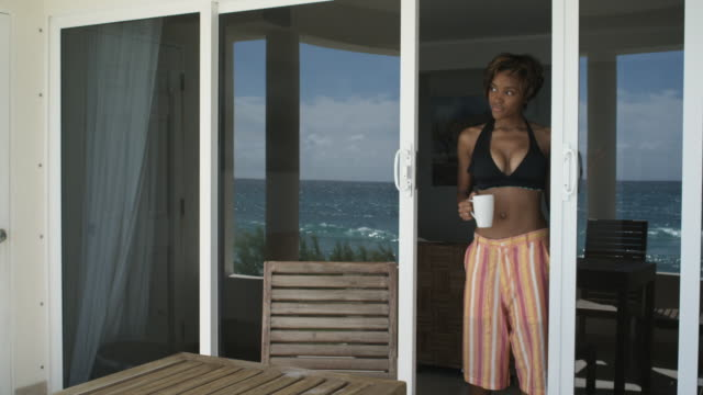 MS Woman coming out door onto patio with cup and sitting down behind table, Atlantic Shores, Bridgetown, Barbados