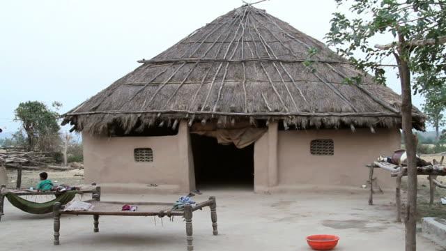 vídeos de stock e filmes b-roll de ws woman coming out of hut at jim corbett national park  / nainital, uttarakand, india - telhado de palha