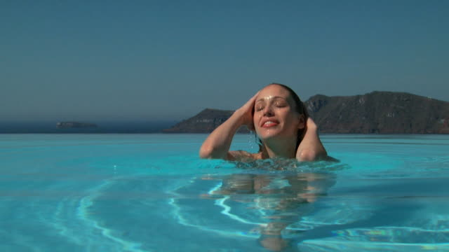 A woman coming up from underwater in an infinity pool