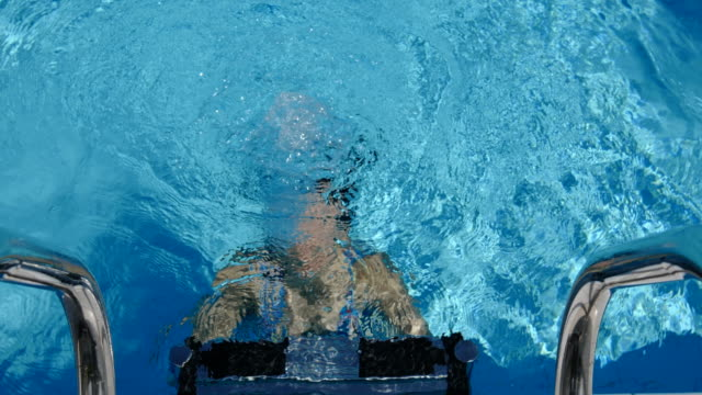 woman coming up from underwater to the ladder in swimming pool - emergence stock videos and b-roll footage