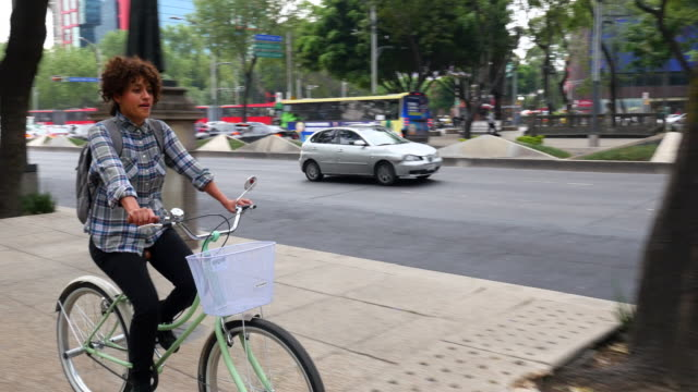 ms ts woman commuting on bike on city sidewalk - curly stock videos & royalty-free footage