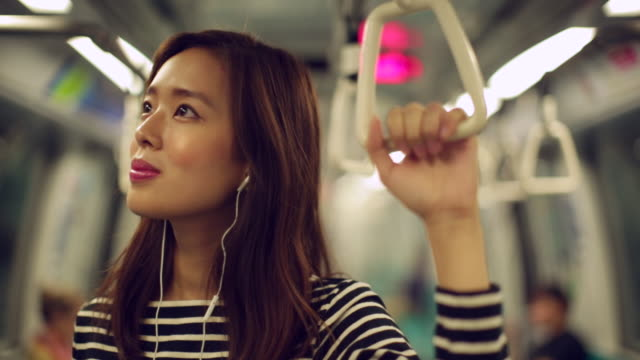 CU Woman commuting on train while listening to music.