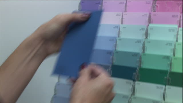 a woman compares blue paint swatches at a store. - color swatch stock videos & royalty-free footage