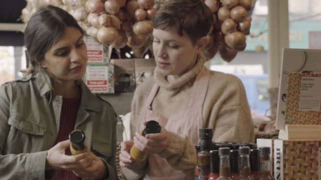 Woman comparing bottles, asks advice of shop assistant in delicatessen shop.