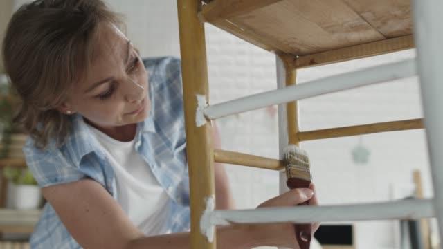 stockvideo's en b-roll-footage met vrouw die terwijl het toepassen van een laag witte verf op oude stoel concentreert - meubels