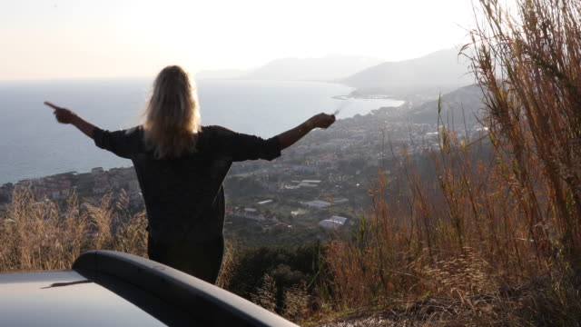 woman 'conducts' to imaginary audience while parked above sea - conductor stock videos & royalty-free footage