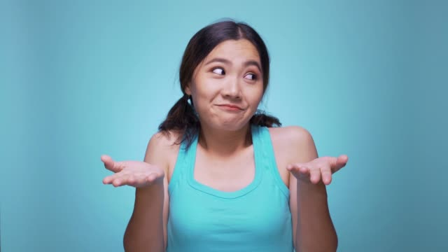woman confused look at camera on isolated blue background 4k - coloured background stock videos & royalty-free footage