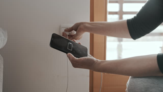 ds woman connecting a mobile phone on a charger plugged into the wall outlet - electrical plug stock videos & royalty-free footage