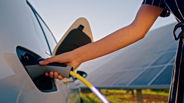 vidéos et rushes de slo mo femme reliant une voiture électrique à l'énergie bleue alimentée par des panneaux solaires - charger activité