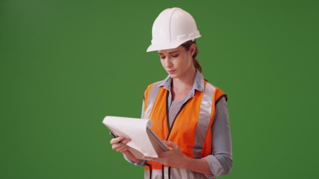 vídeos y material grabado en eventos de stock de woman construction manager writing notes down on her clipboard on green screen - cuello parte de la vestimenta