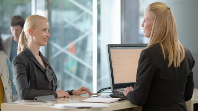 Woman consulting a female bank teller