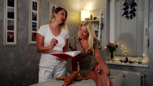 stockvideo's en b-roll-footage met vrouw die met haar masseuse overlegt - massagetafel