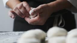Woman cook manually sculpts dumplings stuffed with cherries