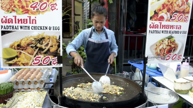 A woman cook Pad Thai, fried noodles in a food stall