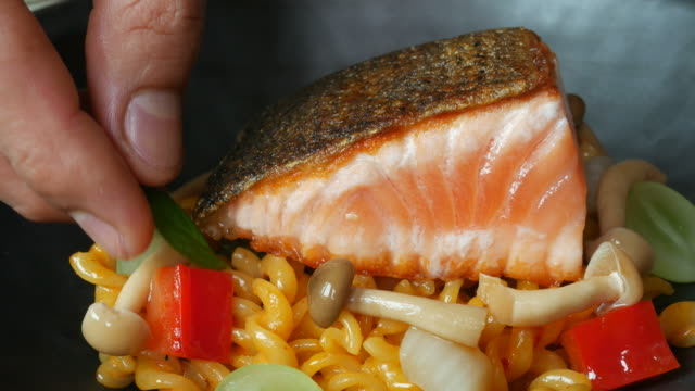woman cook salmon and pasta