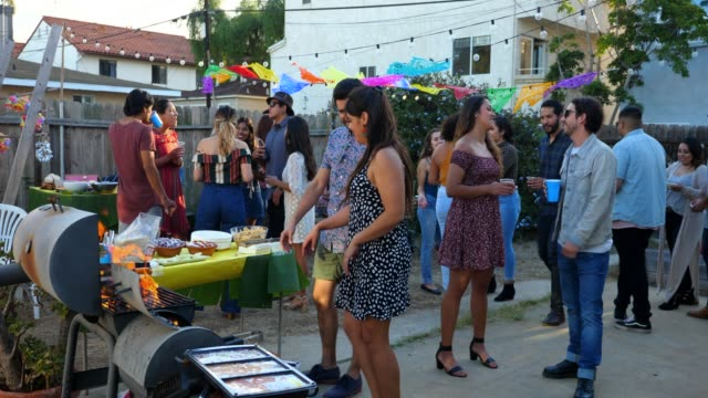 vídeos de stock, filmes e b-roll de ms woman cooking at barbecue during backyard party with friends - public celebratory event