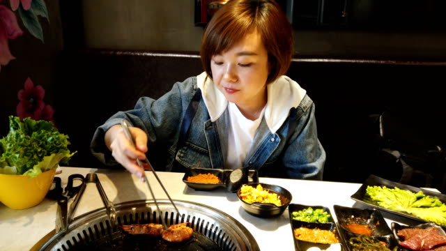 woman cooking barbecue grilled on stove in korea restaurant - coreano video stock e b–roll