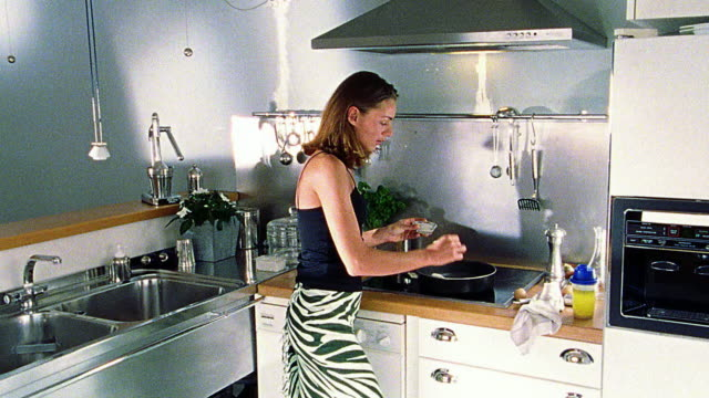 Woman cooking eggs in pan on stove in kitchen