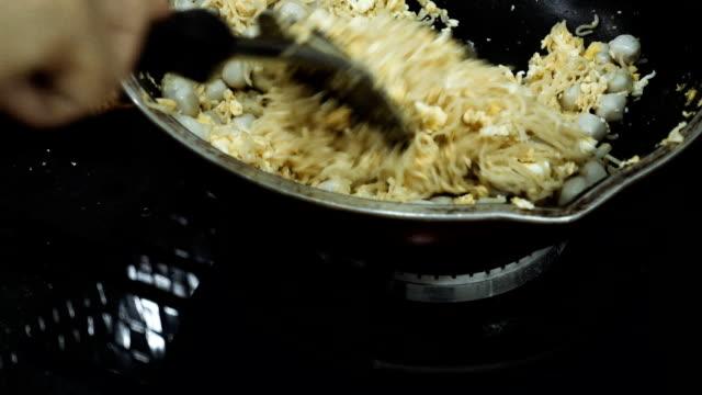 vídeos de stock, filmes e b-roll de mulher cozinhando macarrão frito na cozinha - ovo mexido
