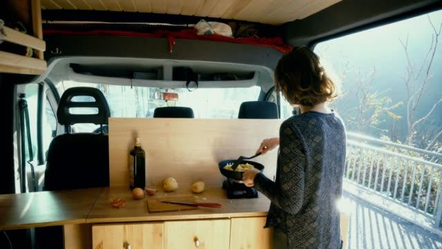 vídeos y material grabado en eventos de stock de mujer cocina patatas fritas en la furgoneta - camping