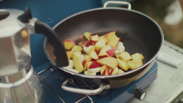 woman cooking fruit in pan on gas stove in front of van - kochgeschirr stock-videos und b-roll-filmmaterial