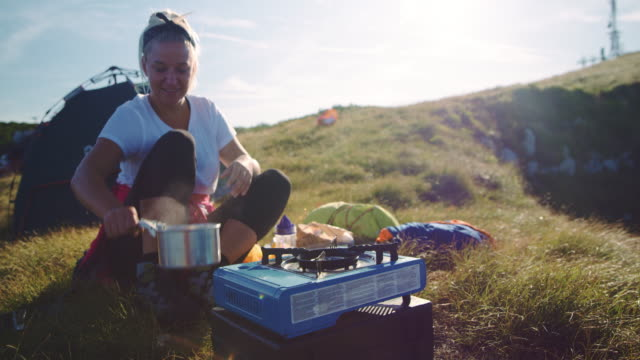 ds woman cooking herself a meal in the camp - stove stock videos & royalty-free footage