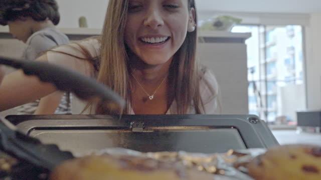 vídeos y material grabado en eventos de stock de mujer cocinando en el horno de la cocina mientras su hijo está en cuarentena en covid-19 - latin american and hispanic ethnicity