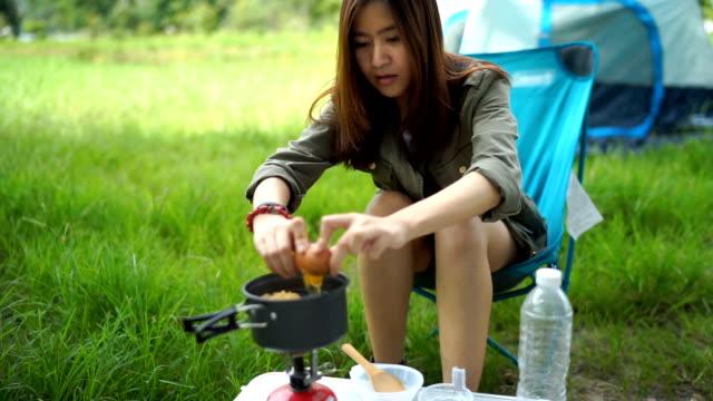 frau koch-instant-nudeln und ei auf dem campingplatz - zelt stock-videos und b-roll-filmmaterial