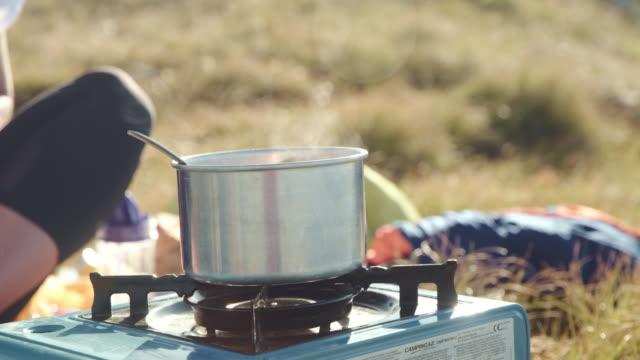 キャンプストーブで料理するmsウーマン - キャンプ用ストーブ点の映像素材/bロール