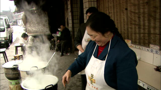 a woman cooking over coal briquettes;   zoom in     burning briquettes.  close shot_chongqing, sichuan province - briquette stock videos & royalty-free footage