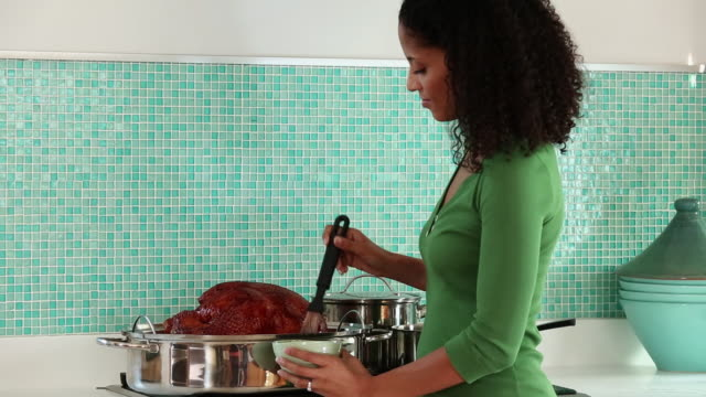 MS PAN Woman Cooking Turkey in Kitchen, Putting in Oven / Richmond, Virginia, USA