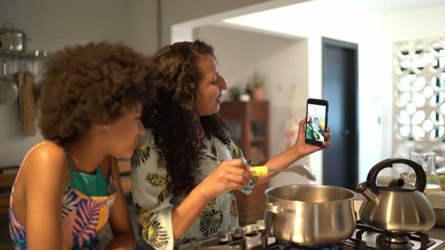 vídeos de stock, filmes e b-roll de mulher cozinhando com a filha e fazendo uma chamada de vídeo o smartphone em casa - preparing food