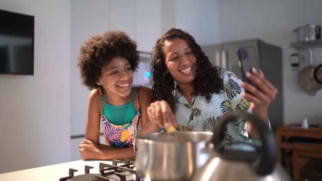 vídeos de stock, filmes e b-roll de mulher cozinhando com a filha e fazendo uma chamada de vídeo o smartphone em casa - film moving image