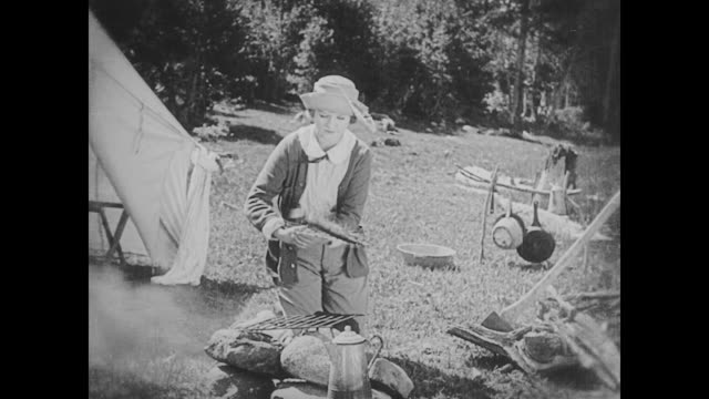 1923 woman (phyllis haver) cooks fish over an open fire - 1923 stock-videos und b-roll-filmmaterial