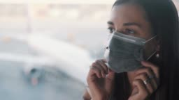 Woman corrects protective medical mask on face in international airport COVID-19