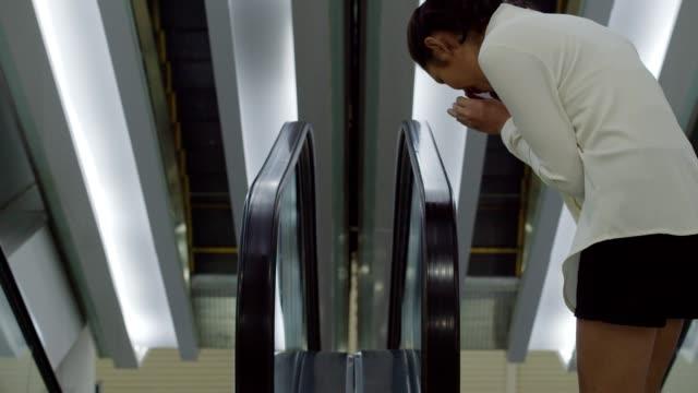 vídeos de stock, filmes e b-roll de mulher tosse pesadamente e toque em trilhos de escada rolante - safety