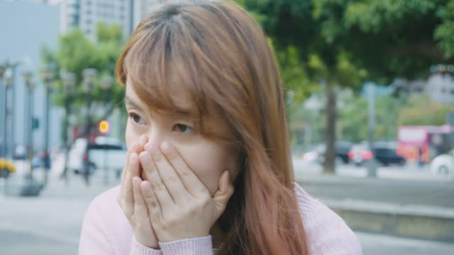 woman coughing and sneezing at outdoor in the city - fischietto video stock e b–roll