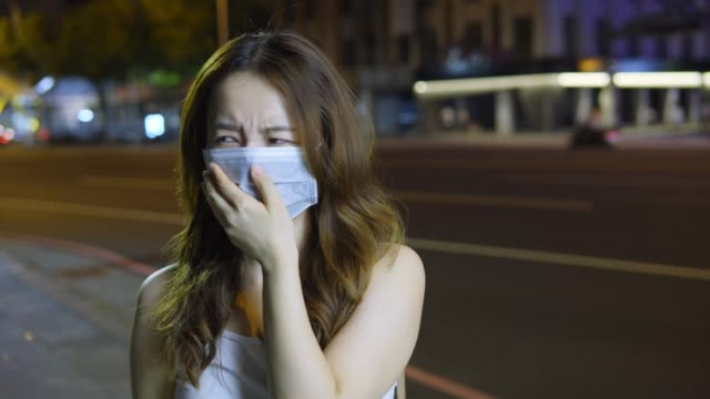 woman coughing and sneezing outdoors in the city - epidemic stock videos & royalty-free footage
