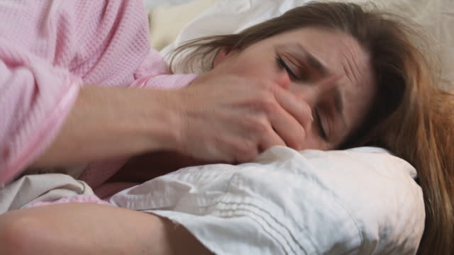 stockvideo's en b-roll-footage met cu woman coughing laying in bed, phoenix, arizona, usa - verkoudheid en griep