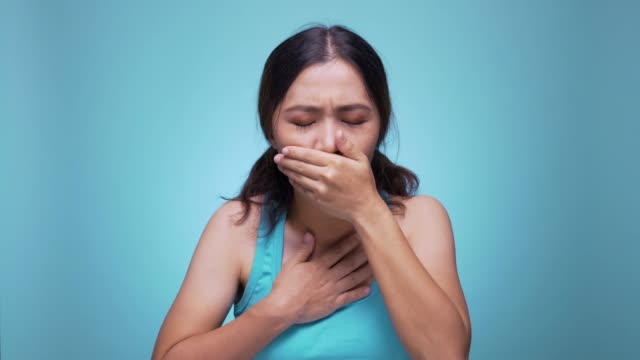 woman coughing on isolated blue background 4k - biohazard symbol stock videos & royalty-free footage