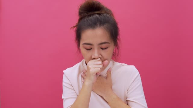 woman coughing on isolated pink background 4k - chinese ethnicity stock videos & royalty-free footage